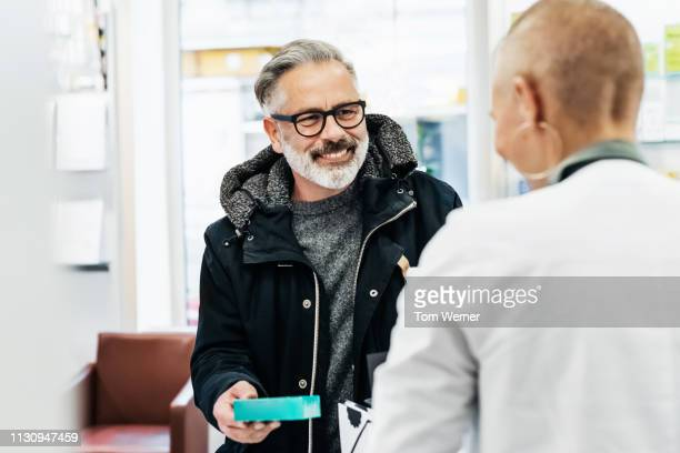 cheerful customer picking up his prescription - prescription medicine stock pictures, royalty-free photos & images