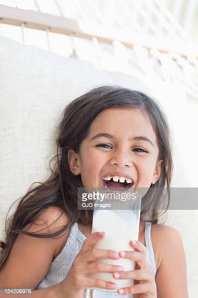 Cheerful cute girl having a glass of milk