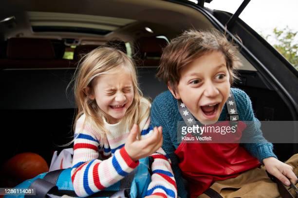 cheerful cute siblings with luggage in car trunk - bruder stock-fotos und bilder