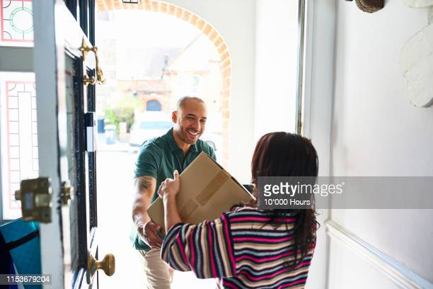 cheerful delivery man handing package to woman - post structure stock pictures, royalty-free photos & images