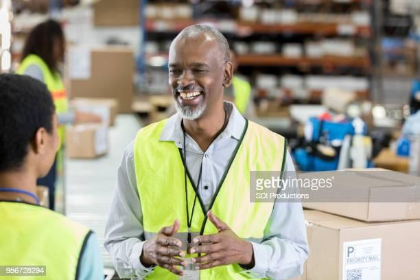 Lager-fröhlich Verteilungs-Manager spricht mit Mitarbeiter