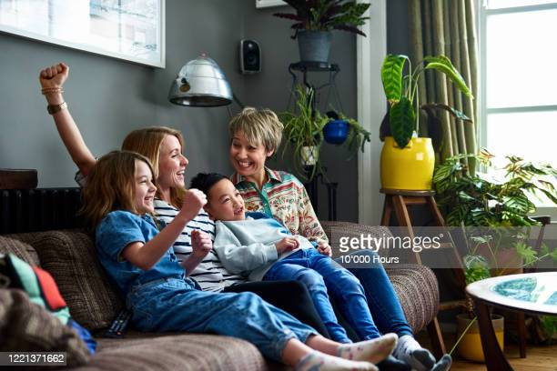 cheerful diverse family with two kids watching television and smiling - bonding stock pictures, royalty-free photos & images