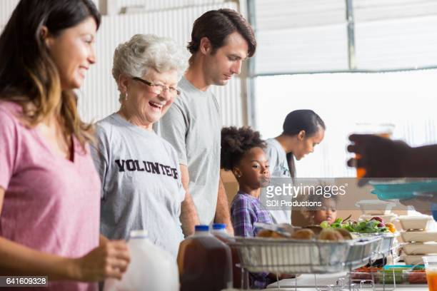 Cheerful diverse volunteers work together in soup kitchen