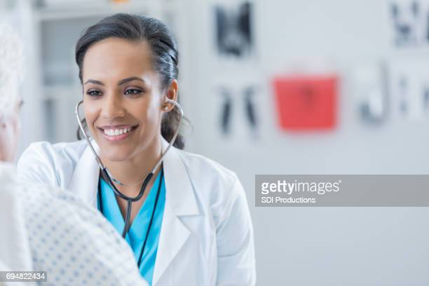 cheerful doctor examines senior man - emergency medicine stock pictures, royalty-free photos & images