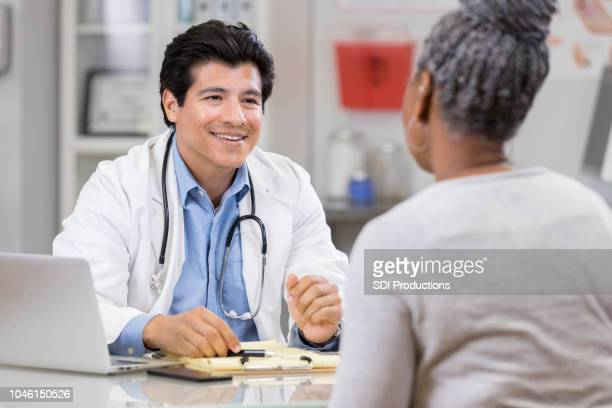 cheerful doctor gives patient good news - handsome doctors stock pictures, royalty-free photos & images