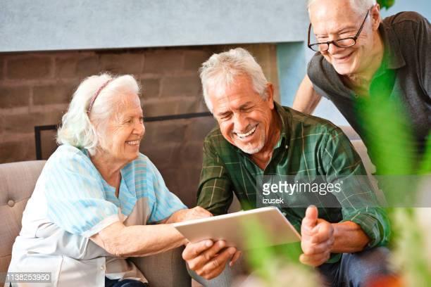 fröhliche ältere freunde mit digitalem tablet - izusek stock-fotos und bilder