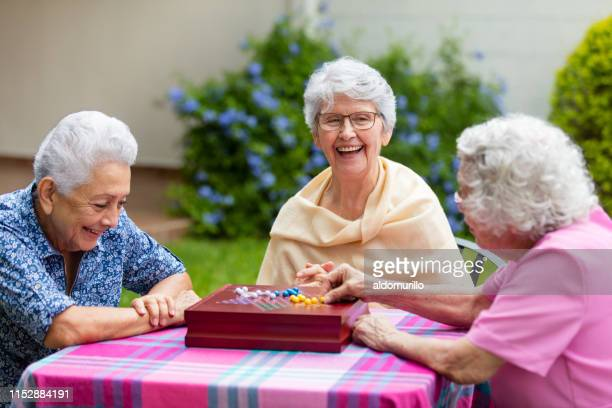 cheerful elderly women playing boardgame outside - leisure games stock pictures, royalty-free photos & images