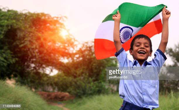 cheerful elementary age child portrait with indian national flag - independence stock pictures, royalty-free photos & images