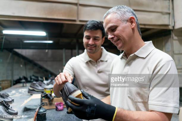 Cheerful employees at a factory checking production of shoes while talking