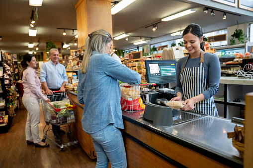 Cheerful employees at supermarket doing checkout for customers 1128048561