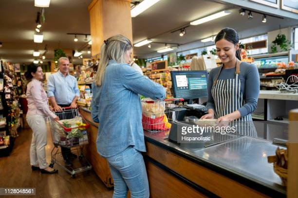 cheerful employees at supermarket doing checkout for customers - cashier stock pictures, royalty-free photos & images