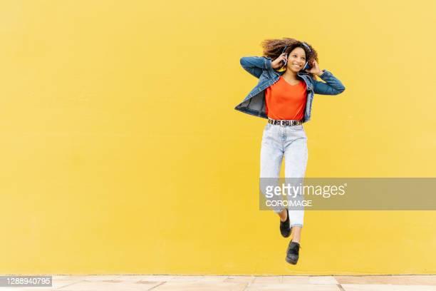 cheerful ethnic woman listening to music and jumping - junge frau allein stock-fotos und bilder