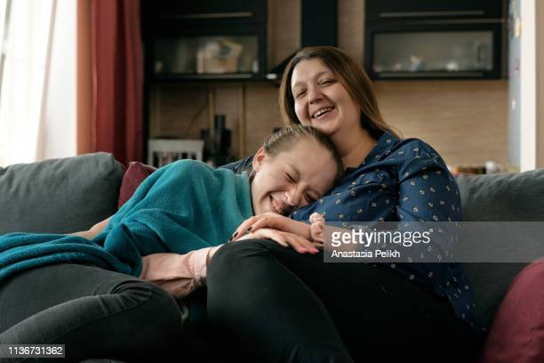 Cheerful excited friendly plus-size mother without makeup and her daughter sitting on sofa at home and laughing at movie while watching TV