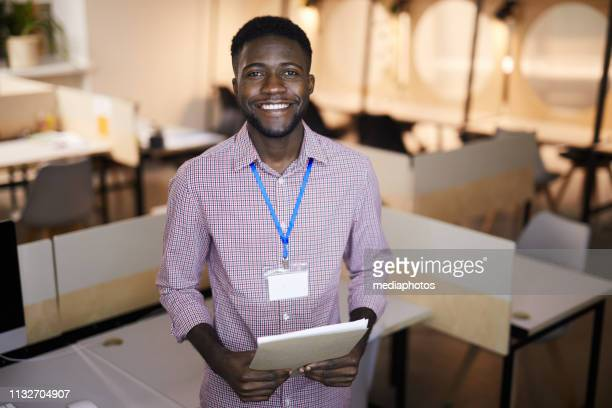 cheerful excited handsome young black guy with stubble wearing blank badge holding notepad and looking at camera while standing in coworking space - wedding planner foto e immagini stock