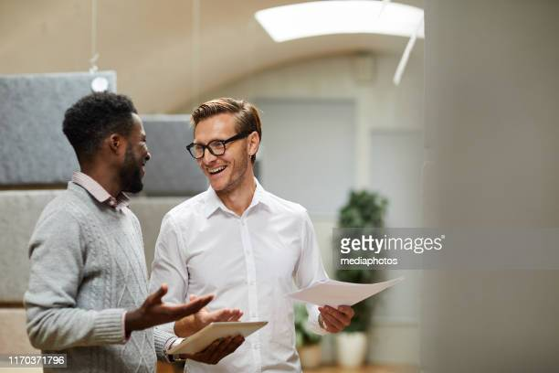 cheerful excited young colleagues standing in modern office and shrugging shoulders while coming to common decision - coworker stock pictures, royalty-free photos & images