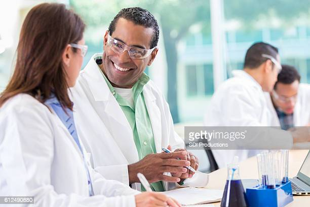 Cheerful experienced scientist talks with colleague