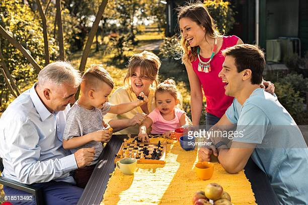 Cheerful extended family playing chess in their backyard.