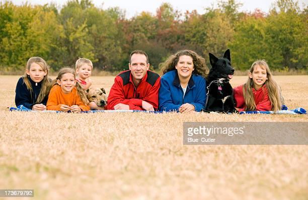 Fröhliche Familie und Hund liegen auf Gras