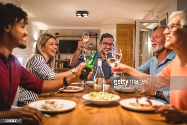 fröhliche familie essen und gäste zu begrüssen - gast stock-fotos und bilder