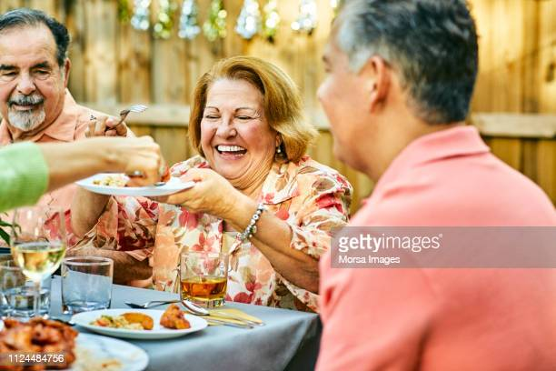 cheerful family eating at table in back yard - southern usa stock pictures, royalty-free photos & images