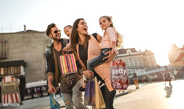Cheerful family having fun during shopping day in the city.