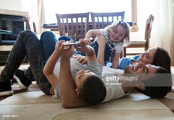 Cheerful family having fun together on carpet.