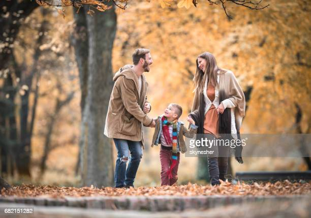 Cheerful family holding hands and communicating while walking in autumn day.