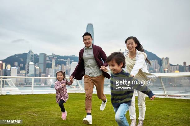 cheerful family holding hands running at park - family with two children stock pictures, royalty-free photos & images