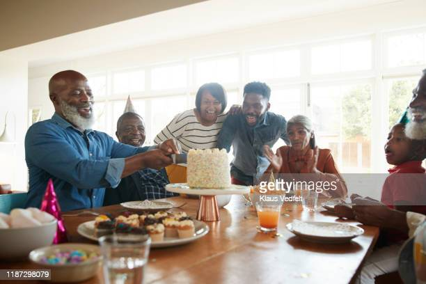 cheerful family looking at man cutting cake at home - softfocus stockfoto's en -beelden