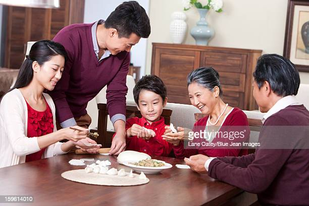 Cheerful family making Chinese dumplings during Chinese New Year