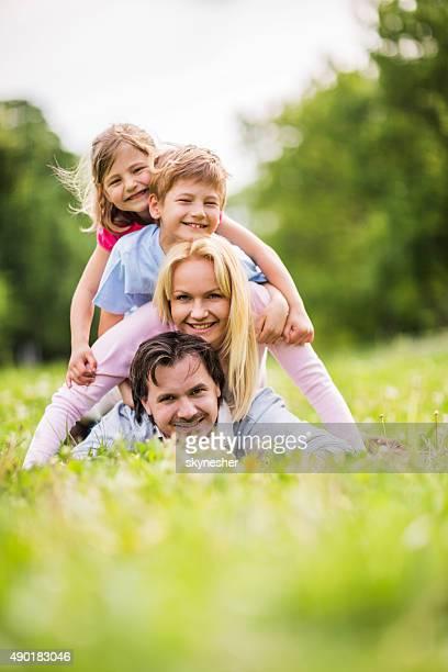 Cheerful family making human pyramid in nature.