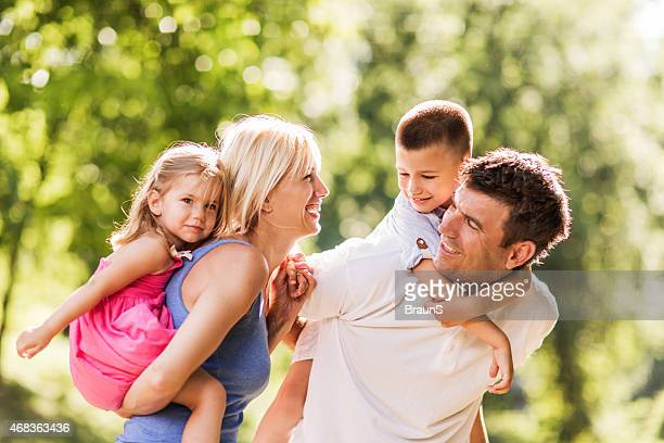 Cheerful family piggybacking outdoors and having fun.