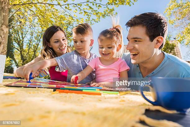 Cheerful family playing board game and having fun in backyard.