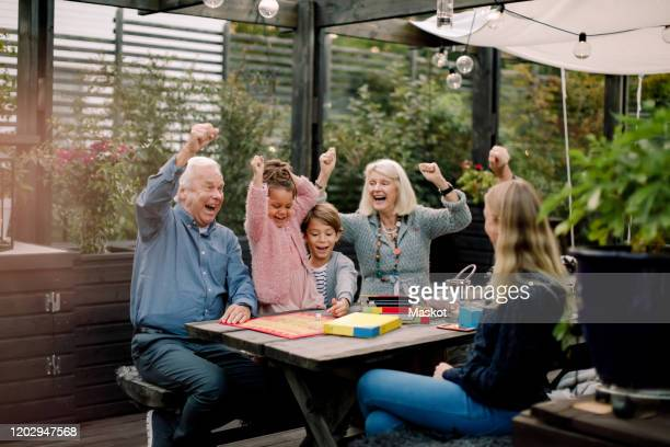 cheerful family playing board game while sitting at table in backyard - board game stock pictures, royalty-free photos & images