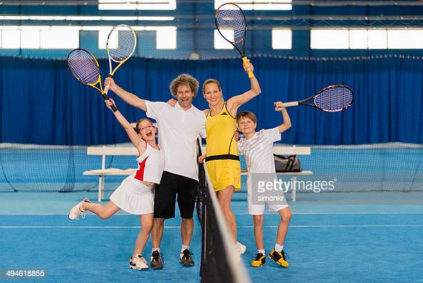 Cheerful Family Playing Indoor Tennis