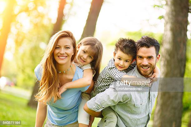 Cheerful family playing piggyback in the park. Looking at camera.
