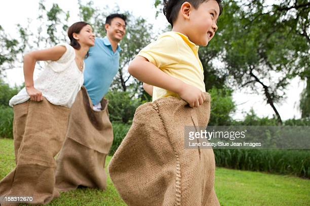 Cheerful family playing sack race