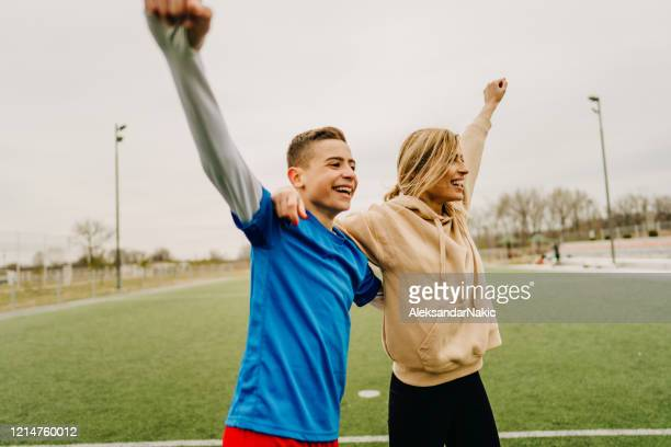 cheerful family playing soccer together - match sport stock pictures, royalty-free photos & images