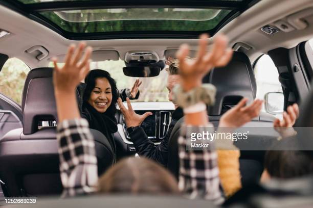 cheerful family raising hands while enjoying road trip in electric car - electric car stock pictures, royalty-free photos & images