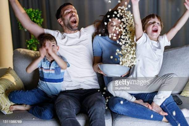 cheerful family screaming of joy while watching sports match at home. - world sports championship stock pictures, royalty-free photos & images