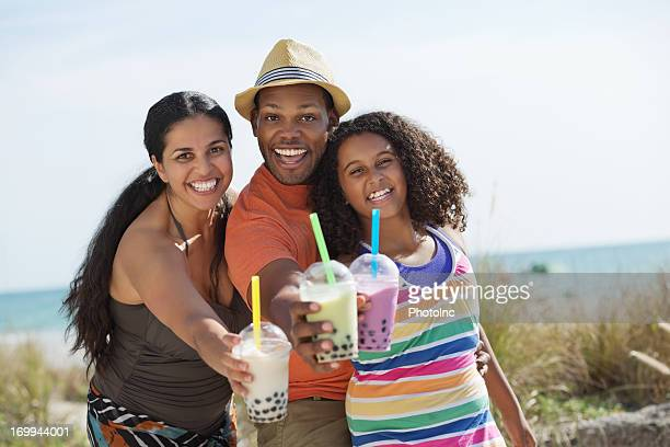 Cheerful Family Showing Bubble Teas At Beach