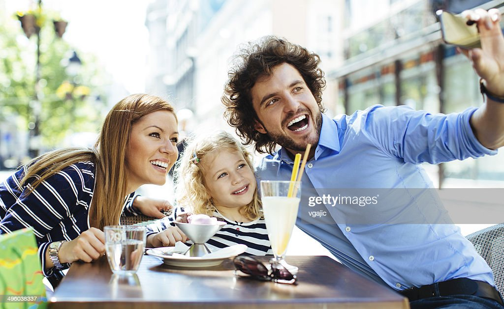 Cheerful Family Sitting In A Restaurant Outdoors And Making Selfie. : Stock Photo