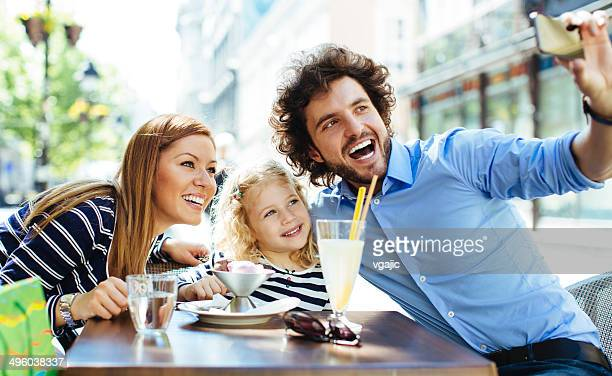 Cheerful Family Sitting In A Restaurant Outdoors And Making Selfie.