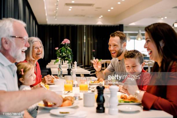 cheerful family talking while having food at table in restaurant - hotel breakfast stock pictures, royalty-free photos & images