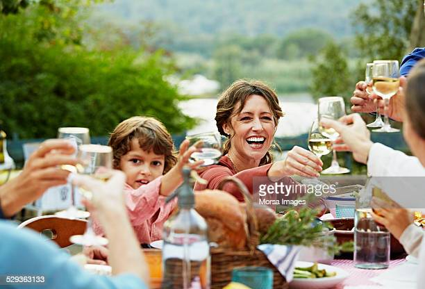 Cheerful family toasting wineglasses in yard