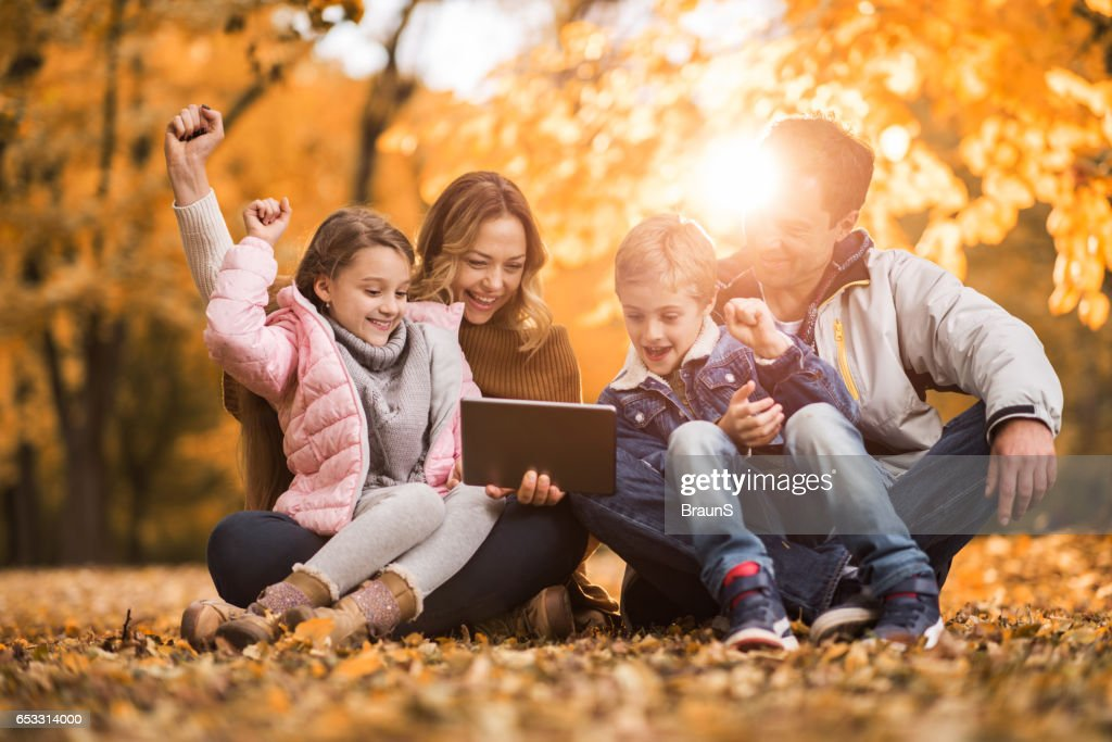Cheerful family using digital tablet in autumn leaves. : Stock Photo