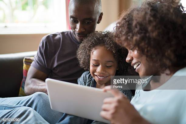 cheerful family using digital tablet on sofa - african american family home stock photos and pictures