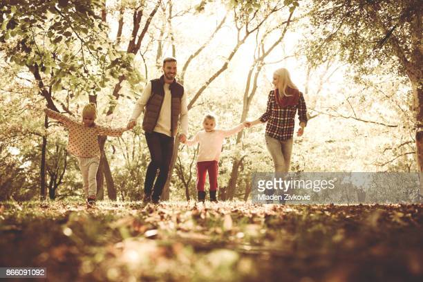 Cheerful family walking trough park together with open arms.