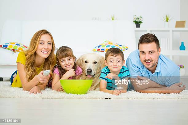cheerful family watching tv. - dog eats out girl stock pictures, royalty-free photos & images