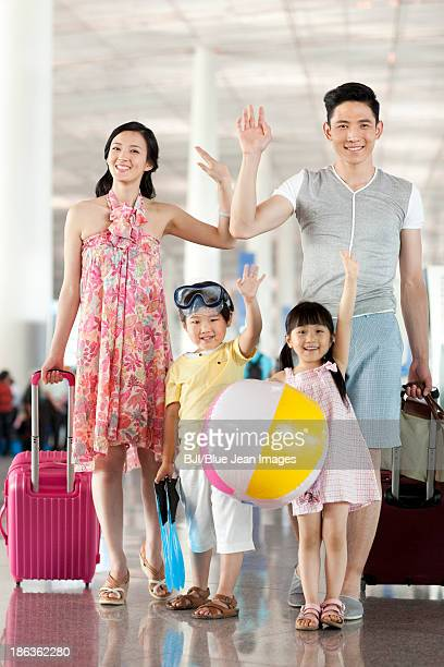 Cheerful family waving at the airport
